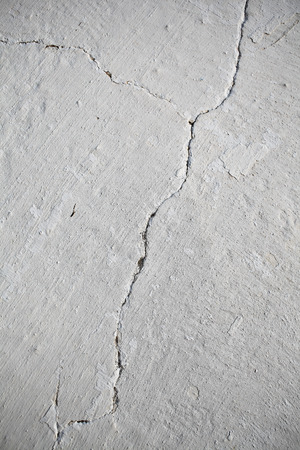 cracks: Textured whitewashed wall with crack.