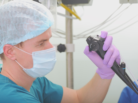 test probe: Conducting of sanation bronchoscopy. Doctor conducting the procedure intently. Stock Photo