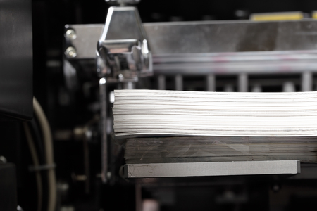 Stack of paper in a printing press.