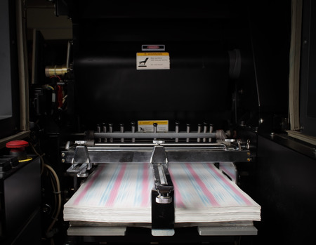 Typographical printing machine with paper in tray.