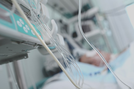 Lifelines in ICU on the background of patient in bed.