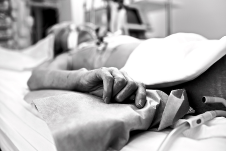 convulsion: Hand of extremely exhausted patients dying in a hospital bed. Black and white conceptual photography. Stock Photo