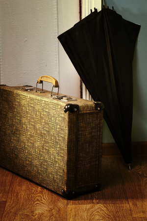 Vintage suitcase and black umbrella on the threshold of the old house. Stock Photo