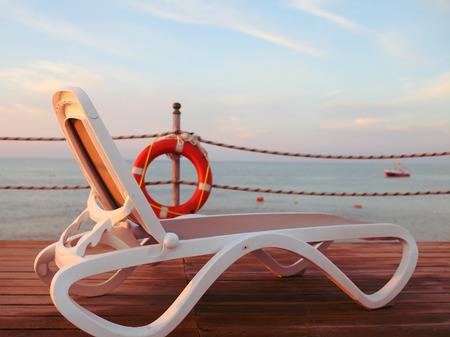 navy pier: End of beach season at sea. Gentle morning sun on a lounger.