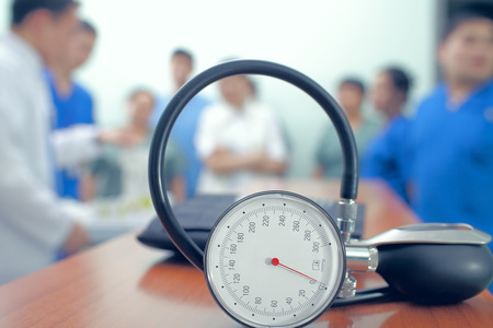 mission: Manometer at the table on the background of group of doctors. Stock Photo
