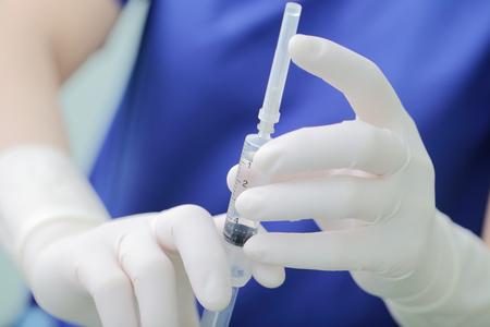 Syringe with drug in doctors hands.