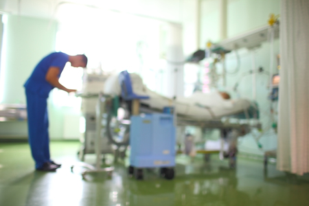 Doctor in the patient ward, unfocused background.