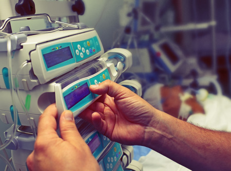 Medical worker configures equipment in ICU.