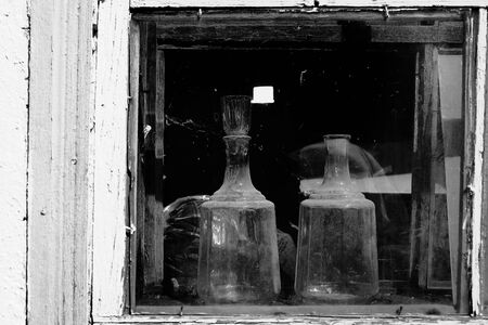 Two kitchen glassware in the window of an old village house. 版權商用圖片