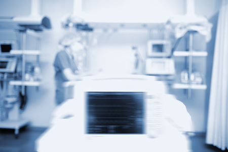Worker in intensive care unit, unfocused background.