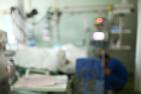 Hospital ward with sitting doctor and patient in bed, unfocused background.