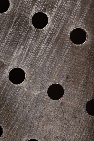 drilled: Grunge metal plate with bores