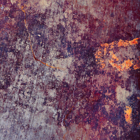 Rusty metal plate with colored spots of corrosion