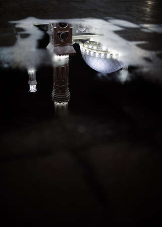 Mosque reflected in puddle water.