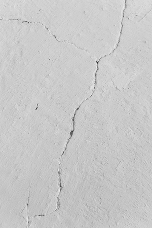 Deep crack in the whitewashed wall.