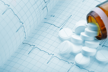 arrhythmias: Medical pills on the background of a cardiogram
