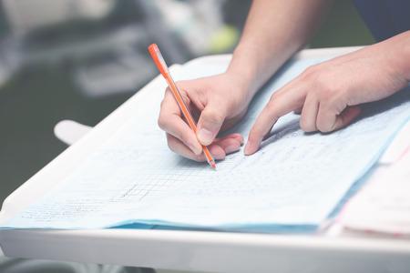 Doctor writing medical report in office. 版權商用圖片