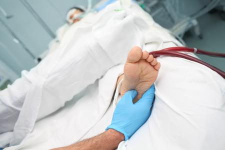 Examination of patient feet in ICU.