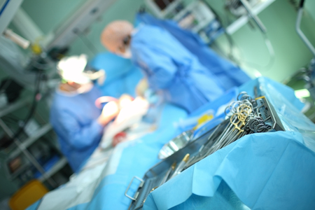 Surgical tools dish on the background of working doctors.