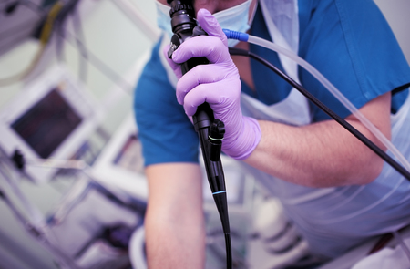 Emergency physician conducts endoscopic testing of ICU patient.