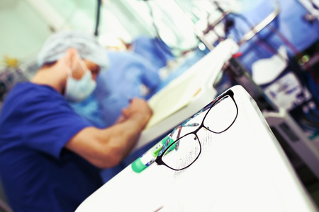 Male doctor writing with spectacles in the foreground.