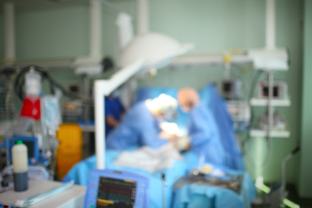 Unfocused background of working surgical staff in hospital.