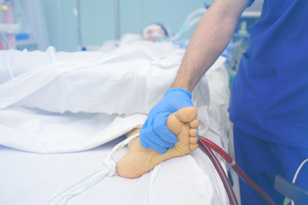 critical care: Doctor palpating patients feet in the critical care.