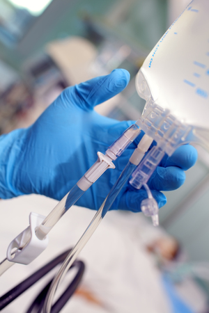 Gloved hand holding intravenous drip in the patient ward. 版權商用圖片