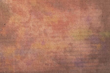 Textured background of colorful stained carton board.