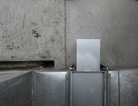 Ventilation shaft on the background of a concrete structure.