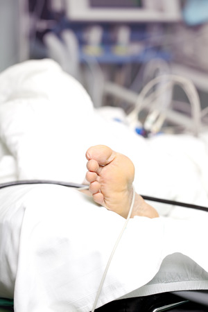 Foot of senior patient lying ih the hospital bed.