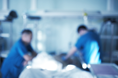 Two male medical workers working with critical condition patient in the intensive care unit, unfocused background. 版權商用圖片