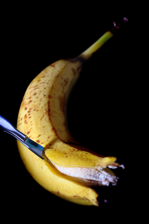 Cutting banana with the surgical knife on the black background.