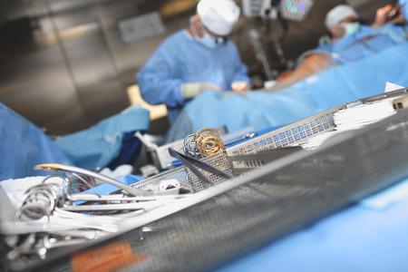 Sterile surgical tools in the dish on the background of working surgeons.