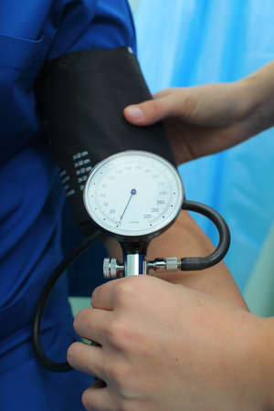 Nurse measures the blood pressure to the patient in the emergency room.