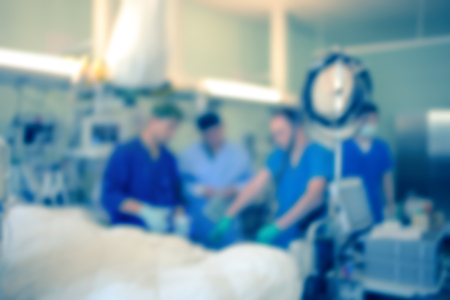 Group of doctors hold consultation at the patients side, unfocused background.