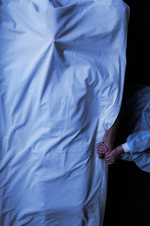Woman holds the hand of a patient who died in a hospital and covered with a sheet.