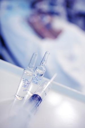 Drug vials and syringe at the patient bedside in the hospital.