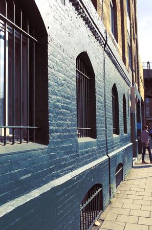 Old retro buiding with iron lattice on the window and painted brick walls. 版權商用圖片