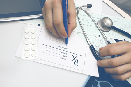 Male doctor fills in the prescription form after examination of patient. 版權商用圖片