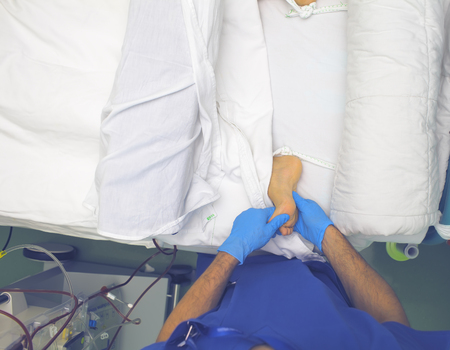Male medical worker massages the feet to the patient with disturbances of the microcirculation of the limbs.