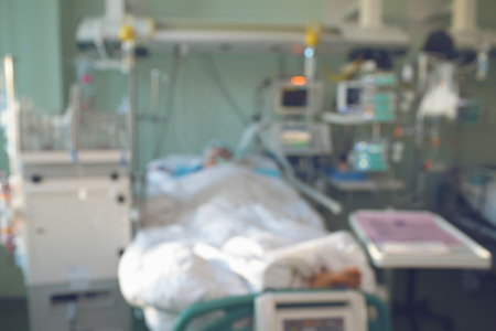 Supportive care for dying patient in the modern equipped ward, unfocused background.