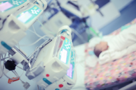 Newborn baby on the bed surrounded by the equipment in the intensive care unit of childrens hospital.