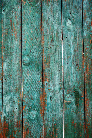 Old close boarded fence painted with sun-faded green color, textured background with space for your text.
