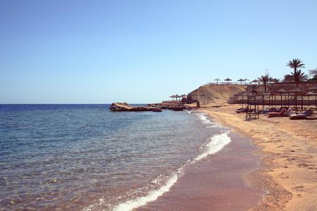 Beach with sun loungers on the seachore. 版權商用圖片