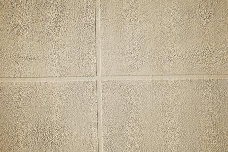 External finishing of concrete wall imitating ceramic tile, textured background.
