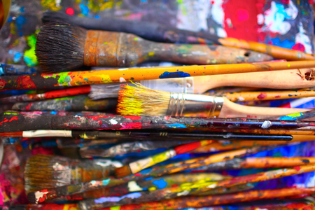 Paint brushes of different sizes, stained by vivid colors, close-up.