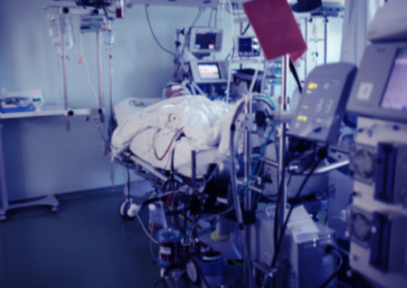 Critically ill comatose patient in the hospital bed connected to the advanced life support equipment in the ICU, unfocused background.