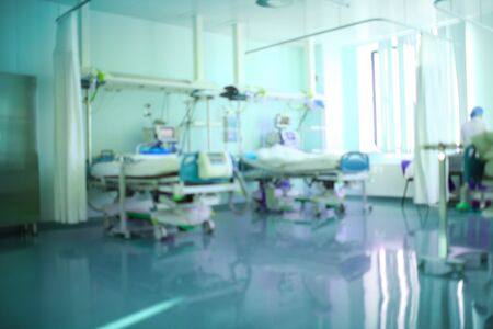 View of intensive care ward with technical equipment and blurred silhouette of medical worker, unfocused background. 版權商用圖片