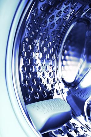 Steel drum of washing machine, textured background.